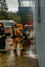 181115-N-SH284-0075 SILVERDALE, Wash. (Nov. 15, 2018) Firefighters for the Bremerton Fire Department hose down a door to cool it prior to entry during a joint live fire training onboard Naval Base Kitsap-Bangor. The joint live fire training brought together firefighters from Navy Region Northwest Fire and Emergency Services, Central Kitsap Fire Rescue, and the Bremerton Fire Department, to practice their skills inside the Naval Base Kitsap-Bangor live fire simulator. (U.S. Navy photo by Mass Communication Specialist 2nd Class Vaughan Dill/Released)