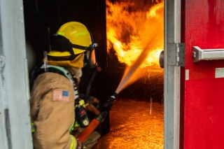 181115-N-SH284-0387 SILVERDALE, Wash. (Nov. 15, 2018) Kyle Davison, a firefighter for Navy Region Northwest Fire and Emergency Services, douses the flames during a joint live fire training onboard Naval Base Kitsap-Bangor. The joint live fire training brought together firefighters from Navy Region Northwest Fire and Emergency Services, Central Kitsap Fire Rescue, and the Bremerton Fire Department, to practice their skills inside the Naval Base Kitsap-Bangor live fire simulator. (U.S. Navy photo by Mass Communication Specialist 2nd Class Vaughan Dill/Released)