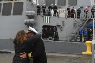 181121-N-YB023-0044 EVERETT, Wash. (Nov. 21, 2018) Cmdr. James Andrew Strickland, commanding officer of the guided-missile destroyer USS Shoup (DDG 86) is greeted by his spouse upon arrival at Naval Station Everett (NSE). Shoup returned to NSE from a cooperative Western Pacific deployment after supporting the Oceania Maritime Security Initiative to enhance regional security and interoperability with partner nations. (U.S. Navy photo by Mass Communication Specialist 3rd Class Clemente Lynch/Released)