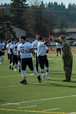 181207-N-SH284-0010 JOINT BASE LEWIS-MCCHORD, Wash. (Dec. 7, 2018) Capt. Alan Schrader, commanding officer of Naval Base Kitsap, gives high fives to Navy team members as they run out onto the field prior to the 19th annual Army/Navy flag football game at Joint Base Lewis-McChord's Cowan Stadium. The game, which is held ahead of the college football rivalry game between the U.S. Naval Academy and U.S. Military Academy, was won by Navy 20-14, marking the sixth consecutive victory for Navy and 13th victory in 20 games. (U.S. Navy photo by Mass Communication Specialist 2nd Class Vaughan Dill/Released)